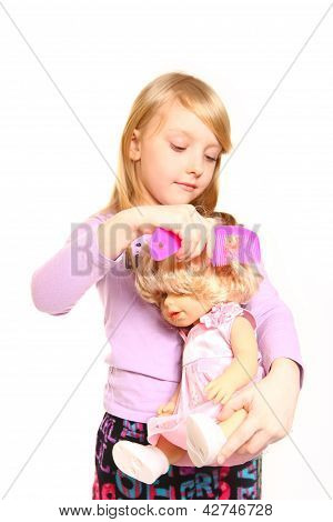 Little Girl Combing Hair Her Doll On A White Background