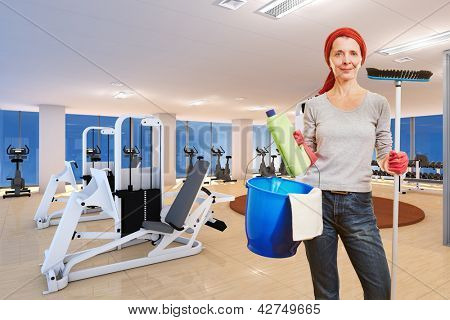 Elderly cleaning lady with cleaning supplies standing in a fitness center