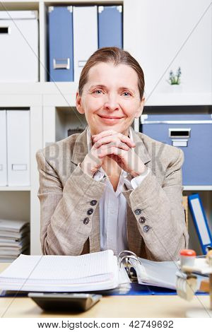 Portrait of happy senior business woman sitting at her desk in the office