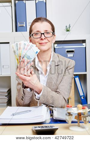 Elderly woman with glasses holding Euro money bills in her office
