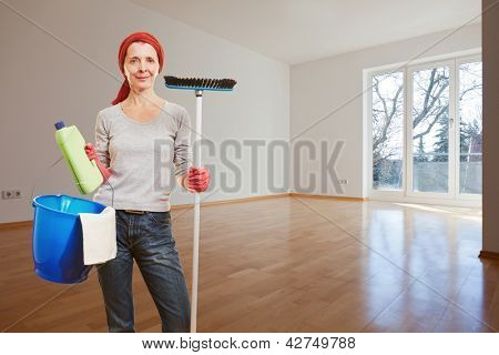 Senior woman with cleaning supplies making spring cleaning in apartment room