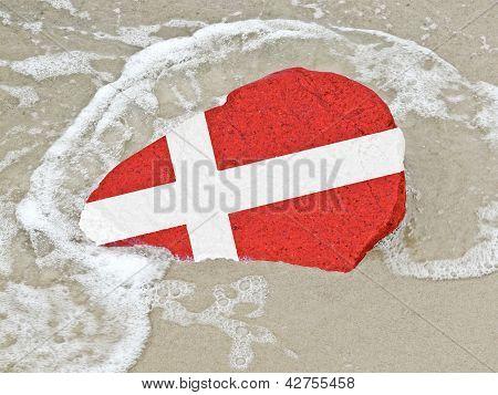 Bandera de Dinamarca en una piedra en la playa