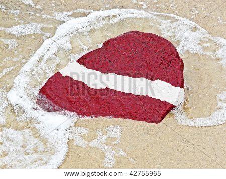 Bandera de Letonia en una piedra en la playa