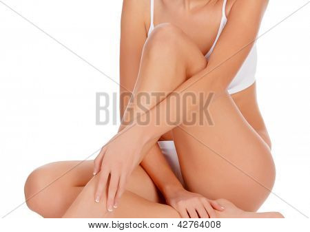 Woman sitting on the floor touch leg by hand, white background