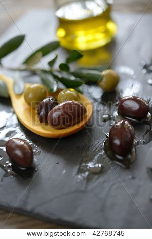 Olives and olive oil on a slate surface