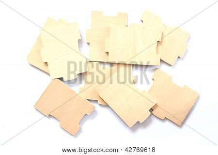 Simple scattered puzzle wooden pieces on white background