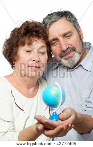 Elderly man and woman look at small globe they hold in their hands