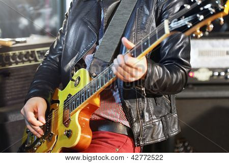 Young man plays electric guitar in studio