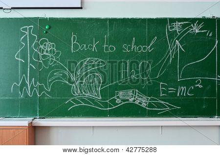 Green chalk blackboard written Back To School with white chalk
