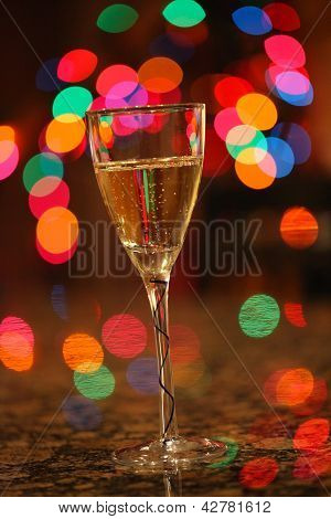 Happy New Year!!! A glass of bubbling champagne with Christmas lights in the background.