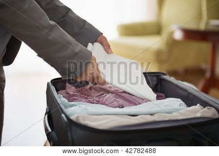 Closeup On Business Woman Unpack Luggage In Hotel Room
