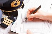 Close up of an airplane pilot hand filling in an flight plan with equipment including hat, epaulette