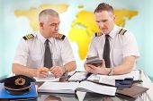 Two airline pilots preparing to flight, checking calculator, papers, flight plan, log book. Pilots a