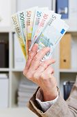 Fan with Euro money banknotes in hand of senior woman
