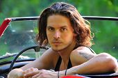 pic of young men  - young man with long hair sitting in a red convertible car and looking straight at the camera - JPG