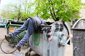 picture of dumpster  - A homeless man looking for food in a garbage dumpster - JPG