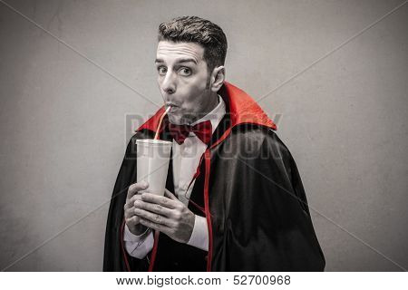 man dressed as Dracula drinking