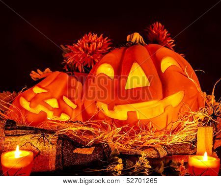 Halloween pumpkin decoration on dark background, traditional autumn scary holiday, bright candle light, dry flowers and terrible spiders