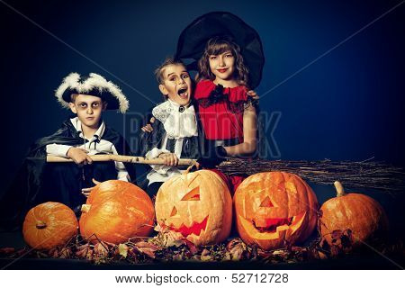 Cheerful children in halloween costumes standing with pumpkins and a broom. Over dark background.