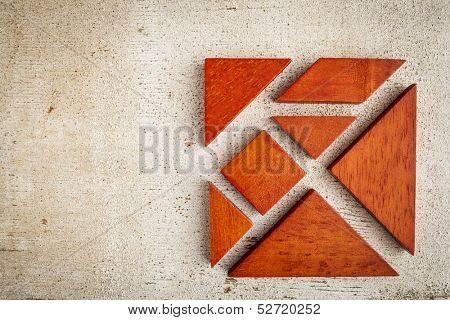 seven tangram wooden pieces, a traditional Chinese puzzle game, rough white painted barn wood background