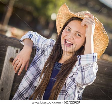 Preteen Girl Wearing Cowboy Hat Portrait at the Pumpkin Patch in a Rustic Setting.