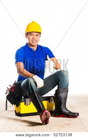Indonesian Asian builder or construction worker with helmet and  tool belt sitting on tool box