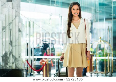 Asian Chinese woman arriving at luxury hotel in business clothes with trolley entering through a glass door into lobby