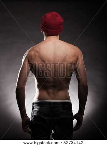 Shirtless back of a young fit and muscular man wearing a beanie hat in a dark background