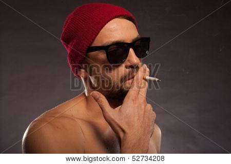 Sexy shirtless bearded man in sunglasses wearing a red knitted beanie cap smoking a cigarette