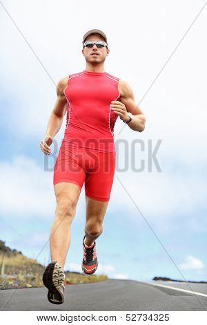 Triathlon running man. Triathlete runner training on Hawaii for ironman. Male athlete running in red compression clothing, shorts and top on volcano on Big Island, Hawaii.