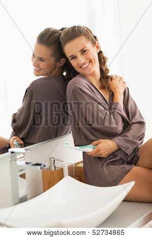 Smiling Young Woman With Toothbrush Sitting In Bathroom