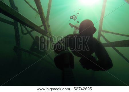 Freediver Going Deap In The Water With A Structure Above Him.