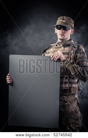 Modern Soldier Is Holding A Poster