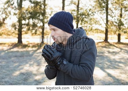 Young man in warm clothing shivering while having a walk in forest on a winter day