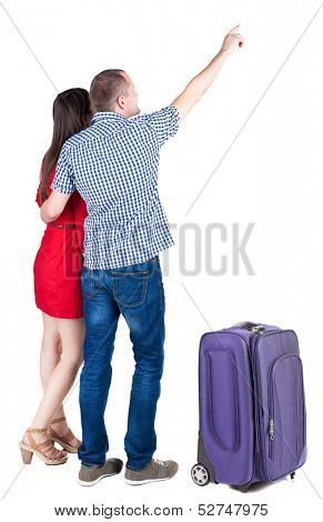 young couple traveling with suitcas and pointing at wal Back view. Rear view people collection.  backside view of person.  Isolated over white background.