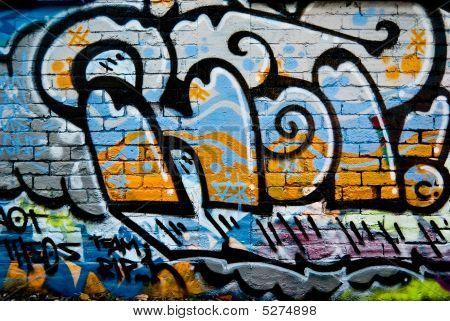 Graffiti Fragment On The Textured Brick Wall
