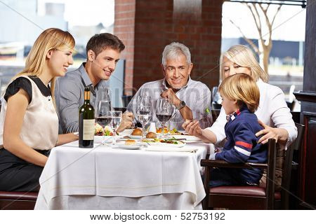 Grandparents feeding their grandchild with a fork in a restaurant