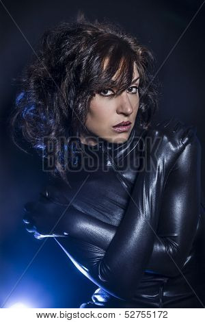 Beautiful brunette woman wearing latex dress on dark background, lying