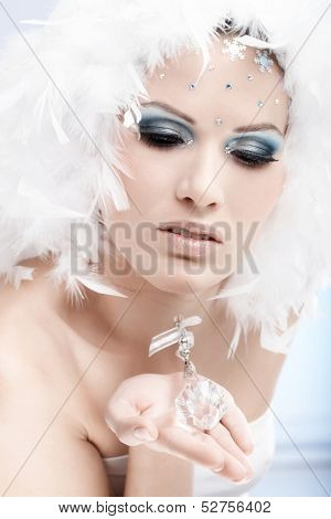 Portrait of winter beauty holding crystal gem, wearing professional makeup with strasses.