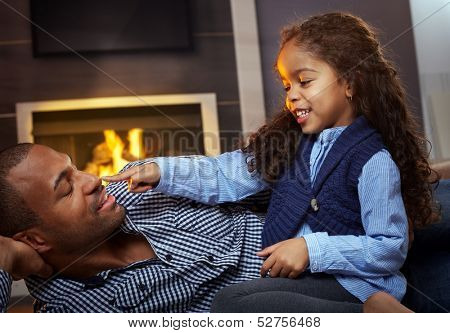 Afro father and beautiful little daughter playing on floor at home, smiling, little girl touching father's nose.
