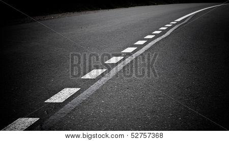 Turning Dark Asphalt Road With Marking Lines. Close Up Photo