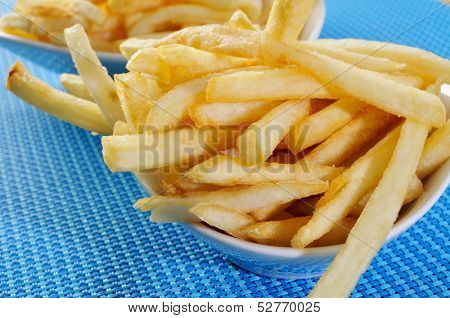 some bowls with appetizing french fries on a set table