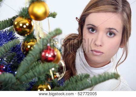 woman posing next to a Christmas tree