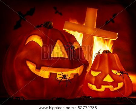 Glowing carved gourd in the hell, burning fire, creepy cross on grave, terrible flying bat, misterious holiday celebration, Halloween party concept