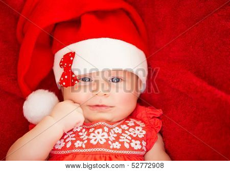 Closeup portrait of cute newborn girl wearing Santa hat, lying down on red background, Christmas holiday, festive baby fashion concept