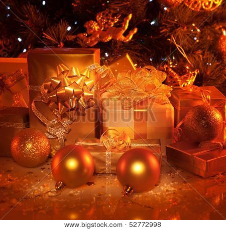 Picture of New Year presents under festive decorated fir tree, many different wrapping gift boxes, Christmastime house decoration, xmas surprise, golden Christmas tree toys, holiday concept