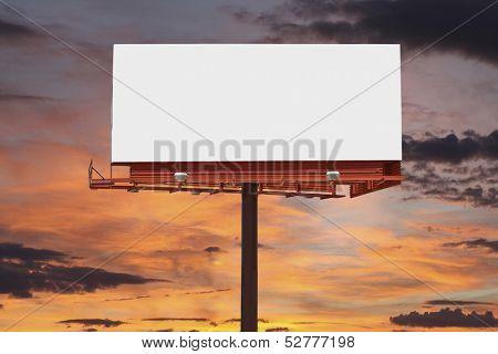 Big blank billboard with orange sunset sky.