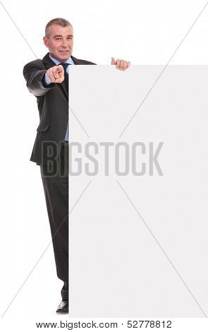 full length portrait of a business man presenting a blank pannel and pointing at the camera. on a white background