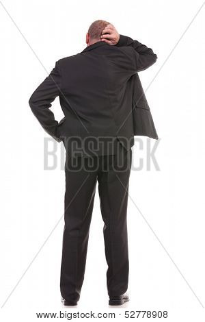 full length back view of a business man standing with a hand in his pocket and scratching his head with the other hand. on a white background