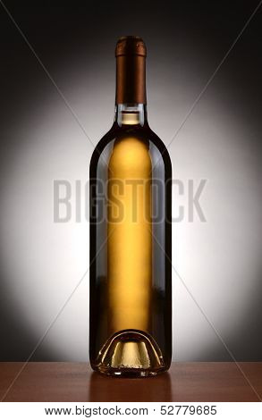 Closeup of a white wine bottle backlit with a light to dark gray background. Vertical Format.
